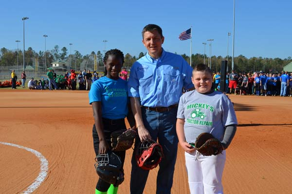 THEY'RE READY TO PLAY, as demonstrated by Desirae Beachem, left, and Dakota Eakin, right, who caught opening baseball and softball pitches thrown by Bainbridge Mayor Edward Reynolds.
