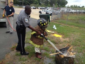 """FIGHTING A FIRE: Dallas Thigpen, a Hutto Middle School student who recently took part in Bainbridge Public Safety's """"Officer for a Day"""" program, puts out a small training fire behind Public Safety headquarters with the help of Sgt. Marvin Knight."""