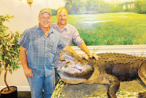 """Troy and Jacob Landry, stars of the """"Swamp People"""" television show, stand next to a Lake Seminole alligator measuring 13 feet, nine inches that was on display at the Bainbridge Country Club, where the father and son were meeting fans and signing autographs on Friday. The show airs on the History Channel on Thursday nights."""