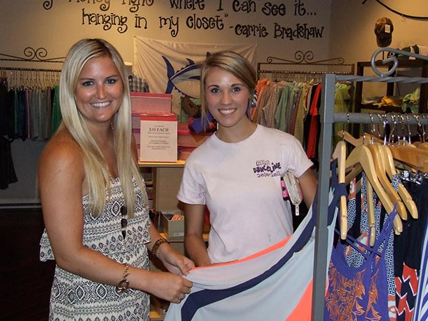 Bella's Boutique associate Sydney Smith, assists BHS senior Caitie Gordon in the selection of a new dress.