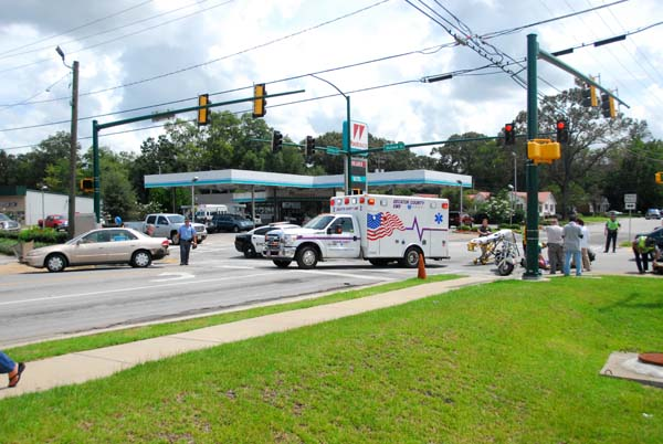 Decatur County Emergency Medical Service personnel and Bainbridge Public Safety officers tend to two people who were injured when their motorcycle was struck by a car at the intersection of Shotwell Street and Sims Street on Friday afternoon.