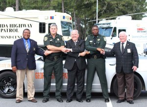 Sheriffs from Florida and Georgia link hands as a sign of support for the Hands Across the Border campaign was held at Bainbridge State College on Monday and Tuesday. From the left, are Early County, Ga., Sheriff William C. Price; Jackson County, Fla., Sheriff Lou Roberts; Decatur County, Ga., Sheriff Wiley Griffin; Gadsden County, Fla., Sheriff Morris Young, and Grady County, Ga., Sheriff Harry Young.