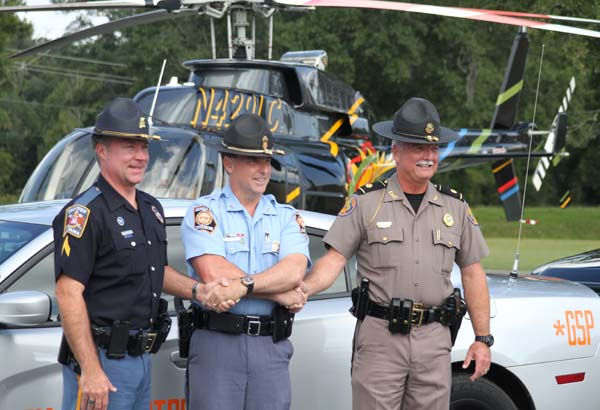 Representatives from the Alabama, Georgia and Florida state highway patrol agencies shake hands as a sign of support during the Hands Across the Border media conference Tuesday at Bainbridge State College. From the left, are Sgt. Steve Jarrett with the Alabama Highway Patrol, Capt. Buddy Johnson from the Georgia State Patrol and Maj. Mark Welch from the Florida Highway Patrol.