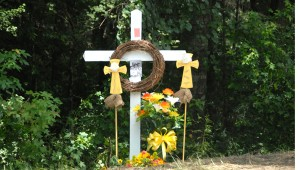 TRAGIC SIGHT: A wooded area on Lake Douglas Road is now adorned with a white cross and some flowers. Handwritten notes were tacked onto the cross, commemorating the three young lives that were lost here in car accident Friday night. Three funeral services were held Tuesday for Adam Goodman, Jordan Harris and Hilary Brock. These services were so crowded they were standing room only.  -- Brennan Leathers