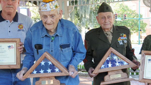 WWII veterans T.P. Bryant, left, and Sgt. Austin Connell stand with their folded flags that have flown over the U.S. Capitol building. The men were honored Friday at Bikefest.