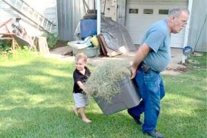 Kash McEwen helps his grandpaw take hay to the horses