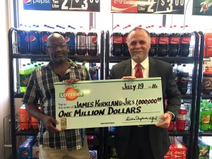 James Kirkland (left) smiles with Jeff Smith and the $1 million prize at Circle K on Dothan Highway.